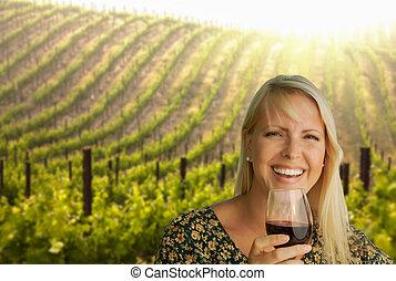 Una joven atractiva con copa de vino en un viñedo.