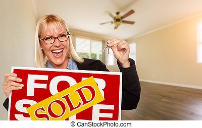 Una joven atractiva con llaves nuevas y vendió un letrero de bienes raíces en una habitación vacía