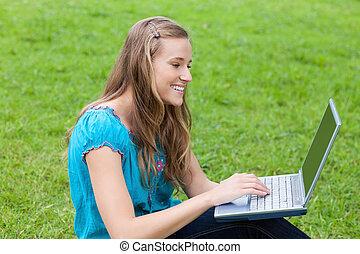 Una joven atractiva mirando su portátil mientras se sienta en la hierba en un parque