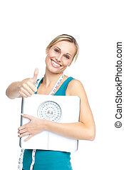 Una joven atractiva sosteniendo una escala de peso