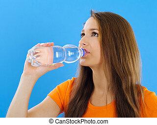 Una joven bebiendo agua embotellada
