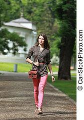 Una joven caminando en un parque