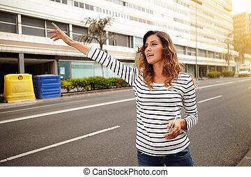 Una joven caucásica llamando a un taxi