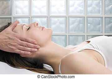 Una joven caucásica que está tumbada recibiendo masaje en la cabeza