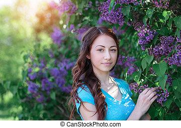 Una joven cerca del arbusto lila en el parque de primavera