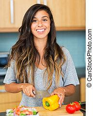 Una joven cocinando. Comida sana
