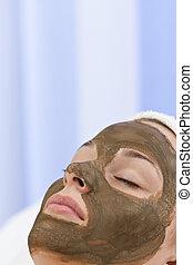 Una joven con máscara de chocolate facial facial en un balneario