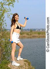 Una joven con pesas haciendo ejercicio al aire libre