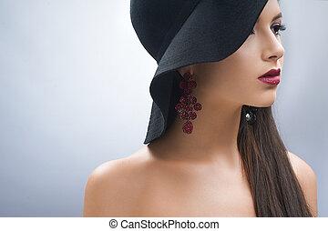 Una joven con sombrero negro.
