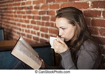 Una joven con taza de café blanco lee su Biblia