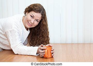 Una joven con una taza naranja en las manos mirando a la cámara en la mesa, en el espacio de copia