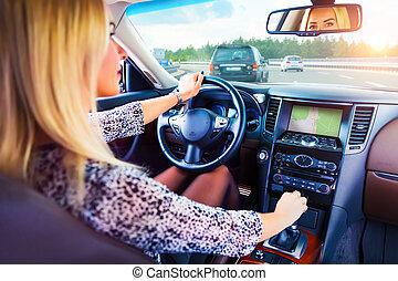 Una joven conduciendo un auto en una autopista
