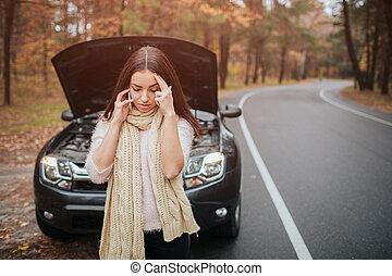 Una joven confundida mirando la reparación de coches rotos en la calle
