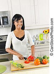 Una joven cortando verduras en la cocina