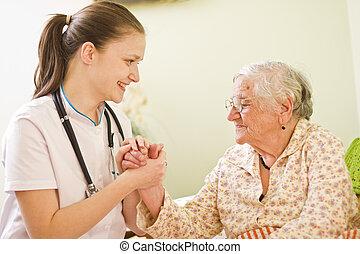 Una joven doctora visitando a una anciana enferma socializando - hablando - con ella, sosteniendo sus manos.