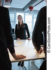 Una joven ejecutiva con colegas alrededor de una mesa
