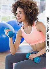 Una joven ejercitando con pesas en el gimnasio