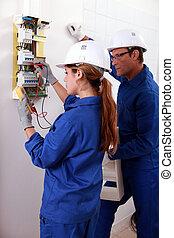 Una joven electricista usando un amómetro para comprobar un contador eléctrico y un hombre mayor vigilándola