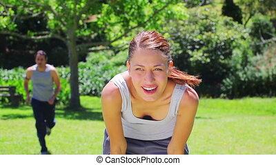 Una joven esperando a su novio después de correr