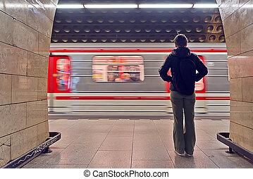 Una joven esperando el tren del metro
