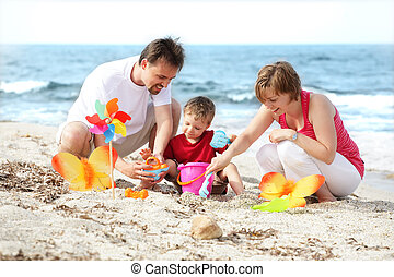 Una joven familia feliz en la playa