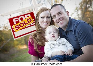 Una joven familia feliz frente a la venta de bienes raíces