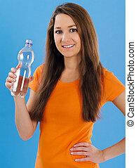 Una joven feliz bebiendo agua embotellada