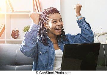 Una joven feliz con la computadora portátil en casa celebrando el éxito