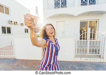 Una joven feliz frente a una nueva casa con llaves nuevas