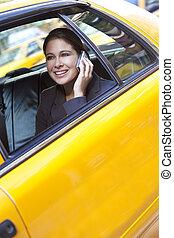 Una joven hablando por celular en taxi amarillo