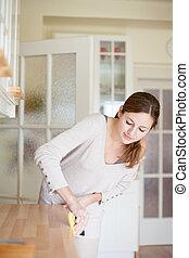 Una joven haciendo tareas domésticas, limpiando la cocina