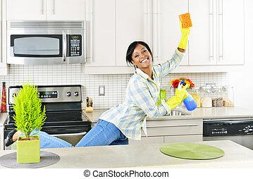 Una joven limpiando la cocina