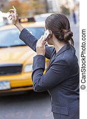 Una joven llamada a un taxi amarillo