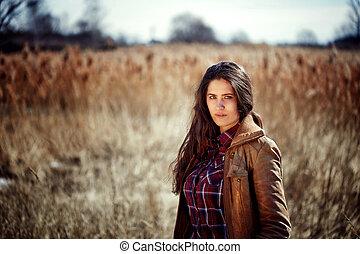 Una joven morena hermosa con el pelo largo y rizado está en un campo.
