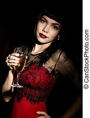 Una joven mujer celebrando con un vestido rojo sosteniendo una copa de champán