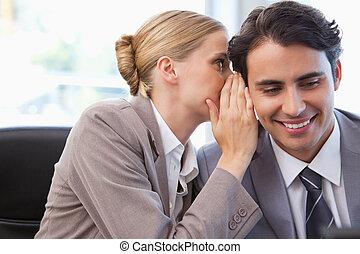 Una joven mujer de negocios susurrando algo a su colega