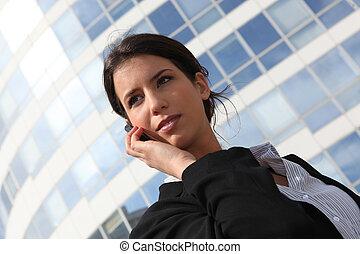 Una joven mujer de negocios usando un celular fuera de un edificio de oficinas