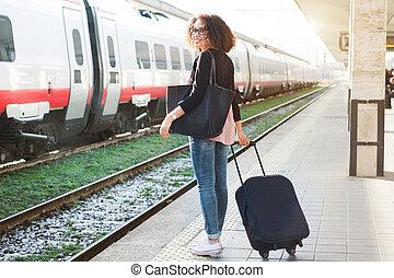 Una joven negra esperando el tren