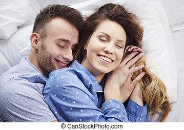 Una joven pareja abrazándose en la cama por la mañana
