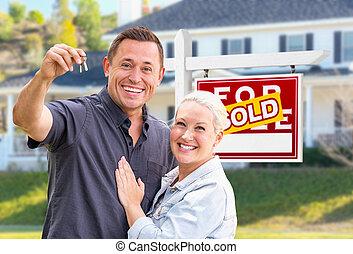 Una joven pareja adulta con llaves de casa frente a casa y vendidas a la venta de inmobiliarias