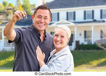 Una joven pareja adulta con llaves de casa frente a una hermosa casa