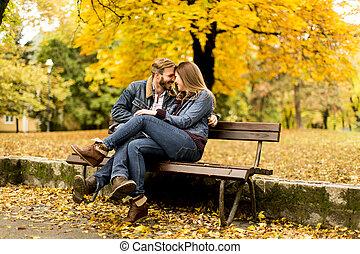 Una joven pareja amorosa en un banco en el parque de otoño