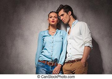 Una joven pareja casual parada cerca de la otra