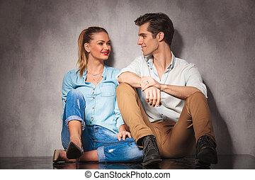 Una joven pareja casual sentada riéndose el uno del otro