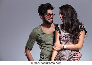 Una joven pareja casual sonriéndose