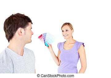 Una joven pareja caucásica eligiendo color para una habitación