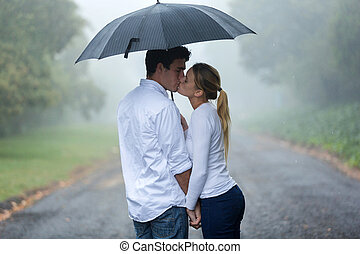 Una joven pareja enamorada bajo la lluvia