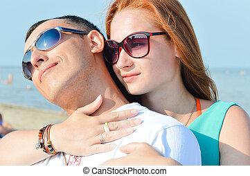 Una joven pareja feliz sentada en la playa arenosa y abrazando con gafas de sol