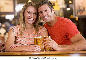 Una joven pareja feliz tomando cerveza en un bar