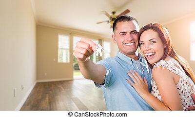 Una joven pareja militar con llaves de casa en la habitación vacía de un nuevo hogar